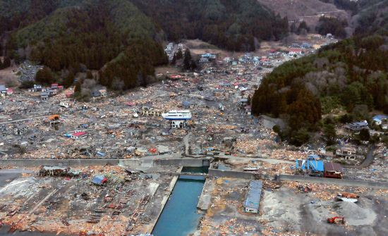 Aerial photo of devastated Japanese village. In the center of the picture is a boat on top of a house.