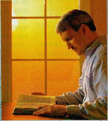 man reading a Bible near a window