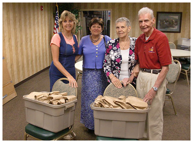 four people with two tubs of paper bags