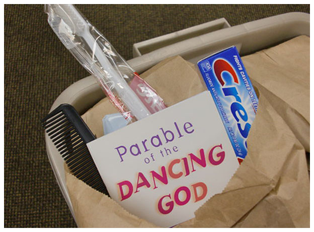 "closeup of paper bag, showing booket ""Parable of the Dancing God"""