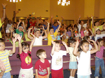 children raising hands at a vacation Bible school
