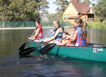 three girls paddling a canoe